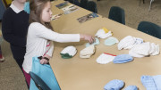 """St. Patrick's students Christabella Gilbank and Natalie Vanderwerken pick out a hat to be placed into a """"Welcome to the World"""" bag as they and classmates make 50 bags to be given to the Lullaby Center at Oneida Healthcare on Tuesday, Feb. 2, 2016 in Oneida N.Y.  (Photo Special to The Catholic Sun by John Haeger)"""